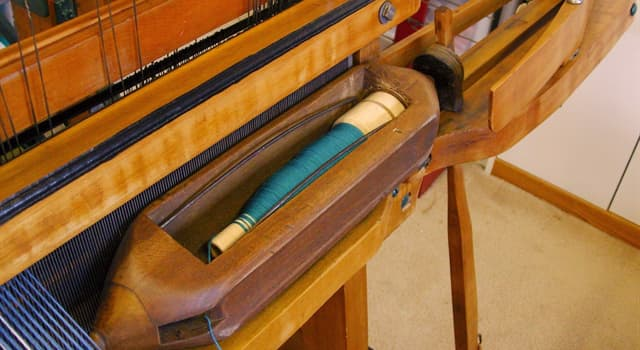 Society Trivia Question: What is a bobbin that carries the thread of the weft yarn while weaving with a loom called?